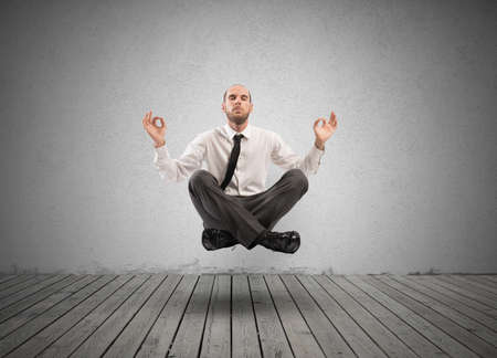 levitation: Concept of relax with businessman doing yoga Stock Photo