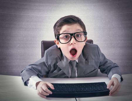 enfants chinois: Ballot enfant choqué travaillant avec un ordinateur Banque d'images