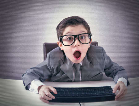 surprised child: Shocked child nerd working with a computer Stock Photo