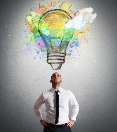 pensamiento creativo: El hombre de negocios iluminado con una idea creativa grande