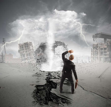Afraid businessman in front of a tornado photo
