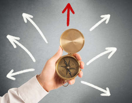 Businessman with compass looking for the correct way