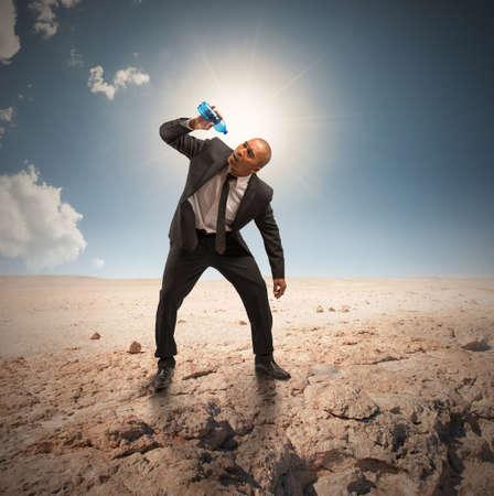 砂漠の空瓶があるビジネスマンの危機の概念