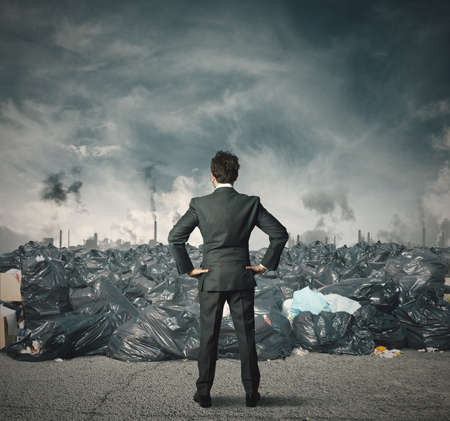 ecological problem: Businessman against a field full of trash Stock Photo