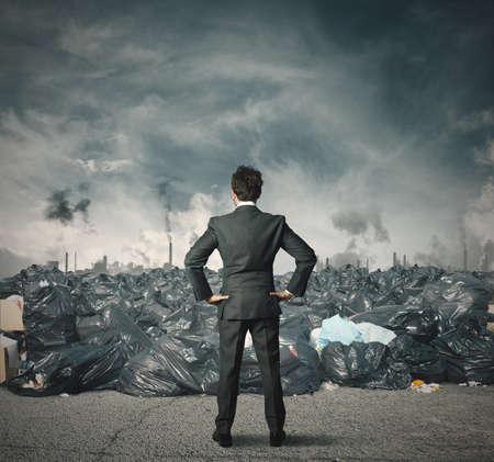 desechos toxicos: El hombre de negocios frente a un campo lleno de basura Foto de archivo