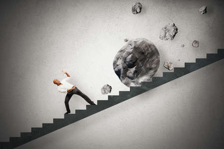 Concept of difficult career of a businessman with falling rocks photo