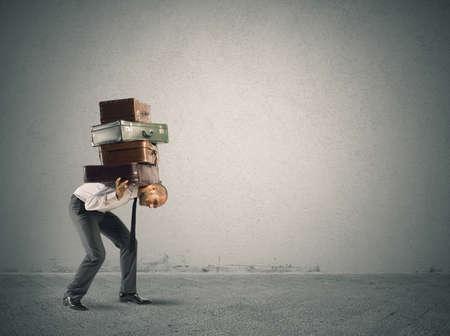 重いスーツケースを運ぶのビジネスマン。難しさの概念