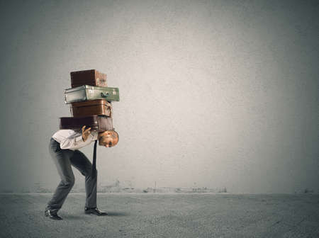 Businessman carrying heavy suitcases. concept of difficulty