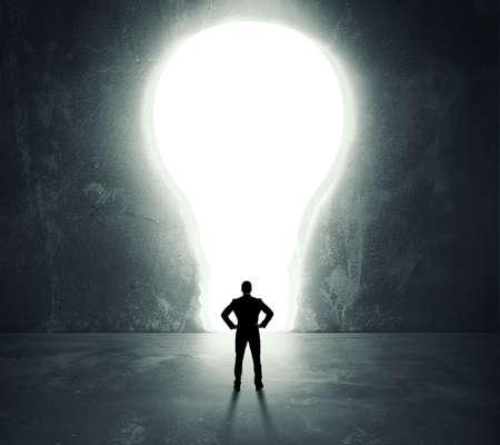 明るい電球のドアの前で実業家