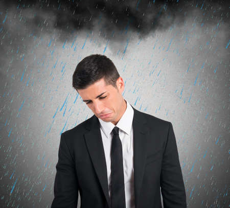 Concept of pessimist businessman for the crisis with a black cloud and rain photo