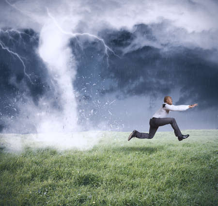 Running businessman escapes from a business storm Stock Photo