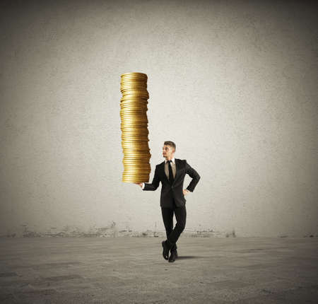 Earn money concept with businessman that holds golden coins photo