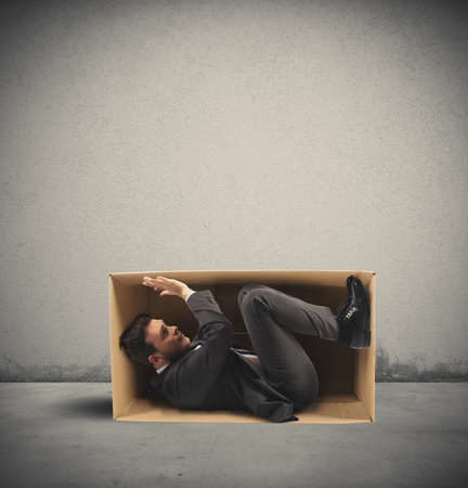 Concepto de trabajo estrecha con un hombre de negocios en el interior de una caja de cartón