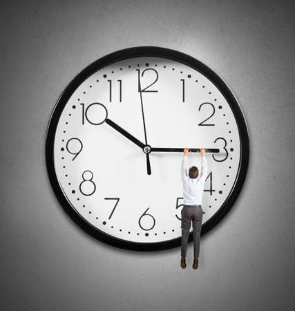 Concept of time with a businessman hanging from the hands of a clock photo