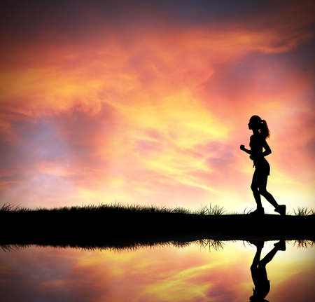 Silhouette of running girl at colorful sunrise photo