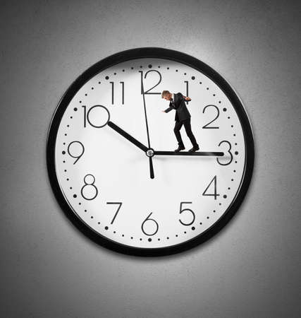 Time concept with businessman above the clock photo