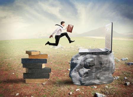 Concept van de technologie migratie met zakenman springen van boek tot laptop