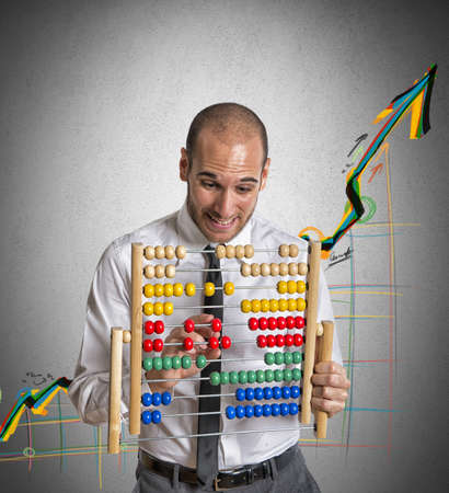 Businessman with abacus calculates a positive trend