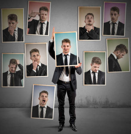 Man selects the smiling face of all the sad faces Stock Photo