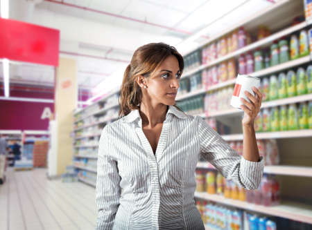 Girl at supermarket with doubt about food photo