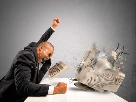 agression: Businessman who breaks  furiously an old computer Stock Photo