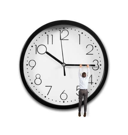 epoca: Concepto de tiempo con un hombre de negocios que cuelga de las agujas de un reloj