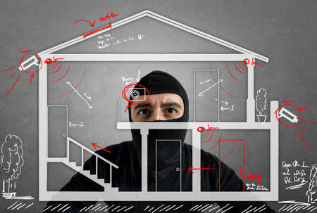 bank robber: Thief apartment studying security system of a new house Stock Photo