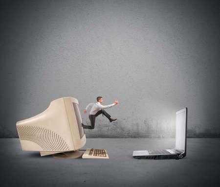 old technology: Uomo d'affari che salta dal vecchio computer al nuovo computer portatile