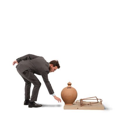 Concept of business trap with businessman taking money from a mousetrap photo