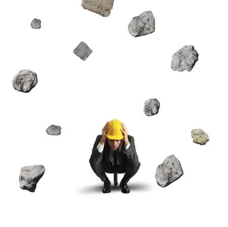 Frightened businessman under the storm of falling rocks photo