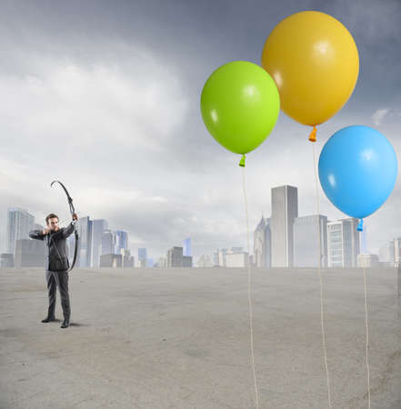 Businessman hits the target with colorful balloon Stock Photo - 30143586