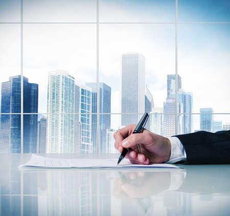Hombre de firmar un contrato de negocios en un escritorio Foto de archivo