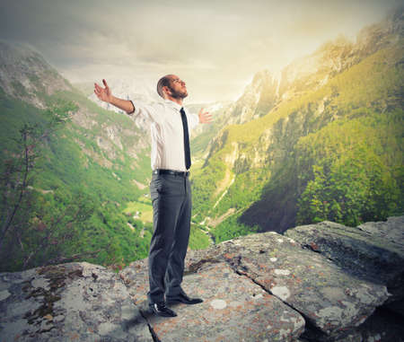 Freedom businessman against a mountain and green panorama photo