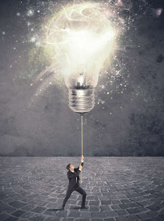 Concept of illuminate an idea with a businessman and big lightbulb photo