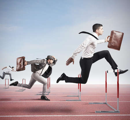 Business competition with jumping businessman over obstacle photo