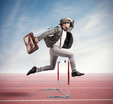 Businessman jumping an obstacle during work Stockfoto