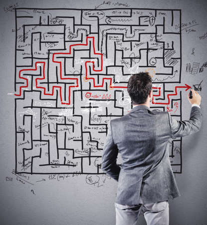 Businessman drawing the solution of a difficult maze photo