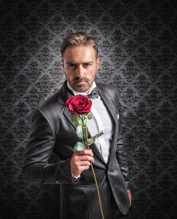 gives: Gentleman gives a red rose on the anniversary Stock Photo