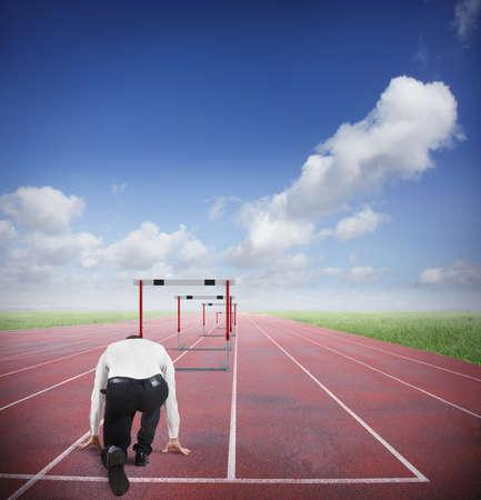 successful people: Uomo d'affari correre a saltare ostacoli di business in una traccia