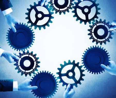 merging together: Teamwork and integration concept with businesspeople that holds gears