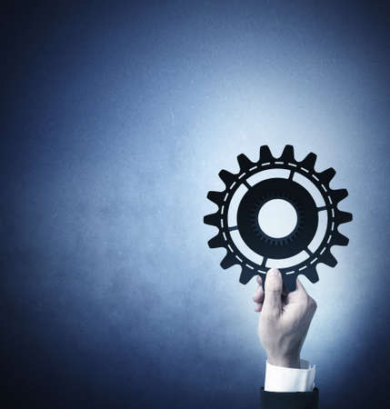 Teamwork and integration concept with businessman that holds a gear photo