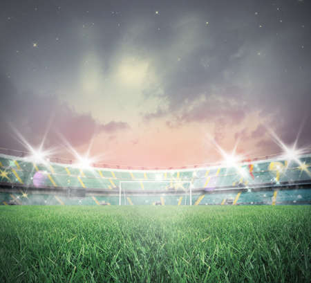 on the ground: Illuminated soccer stadium during sunset with green grass Stock Photo