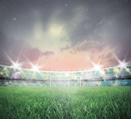 terrain foot: Stade de football éclairé au coucher du soleil avec l'herbe verte