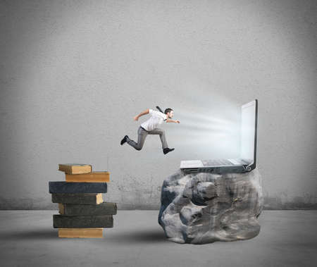 Concept of technology migration with businessman jumping from book to laptop photo