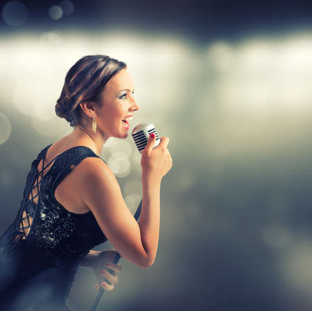 Young sexy singer with retro style microphone photo