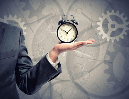 Concept of time with businessman that hold an alarm clock Imagens