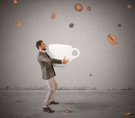Businessman picks with cup coffee beans that fall photo