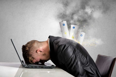 Stressed businessman with explosion of discharged battery Stock Photo
