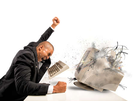 worried businessman: Businessman who breaks  furiously an old computer Stock Photo