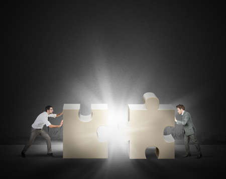 merging together: Teamwork and partnership concept of two businessman Stock Photo